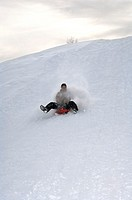 Child sledding down a hill