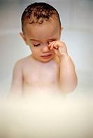 Little boy rubbing eye in bath