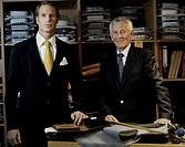 Two well-dressed men in front of a shelf with chemises