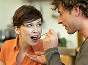 Mid adult man with curly hair feeds his girlfriend with a spoon, close-up