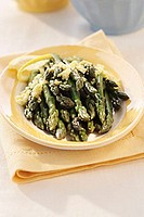 Steamed green asparagus on yellow plate