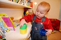 16 month old boy playing with cups (twin brother of twin picture no. J38-507000)