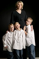 Mother with three boys (6-7), (8-9), posing in studio, portrait