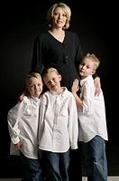 Mother with three boys (6-7), (8-9), posing in studio, portrait