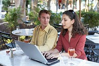 High angle view of a young man looking at a young woman working on a laptop