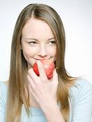 Teenage girl (14-16) holding apple, close-up