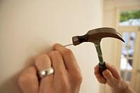 Man hammering nail into wall, close-up