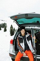Man sitting on boot of car on snow, holding skis, smiling, portrait