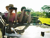 Couple on safari in 4x4 using binoculars