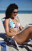 Young woman reading on beach, smiling, side view, close-up