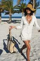 Woman walking with handbag on beach, smiling