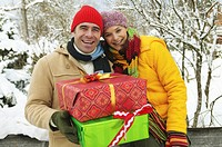Mature couple in snow, man holding presents, smiling, portrait