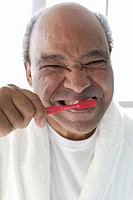 Senior man brushing teeth, portrait, close-up