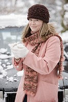 Woman holding snowball, smiling, portrait, close-up