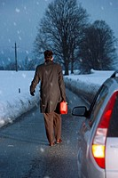 Man carrying petrol can walking in snow away from car on country road