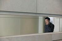 Businessman in hallway using mobile phone