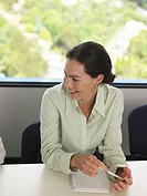 Young businesswoman in meeting, smiling