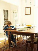 Boy (4-6) sitting at dining table, writing