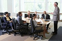 Businessman delivering presentation to executives in boardroom