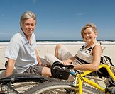 Mature couple sitting on beach by bicycles, smiling, portrait