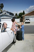 Grandparents in driveway loading car trunk with grandsons (3-5)