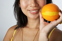 Woman holding orange, smiling