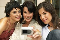 Three women taking photograph of themselves, smiling