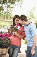 Young couple looking at a potted plant