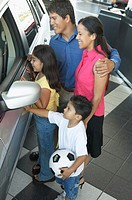 Young couple with children (3-5) in car showroom, elevated view