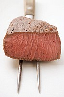 Beef steak, a piece cut off, on meat fork (thumbnail)
