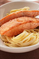 Fried salmon fillets on spaghetti