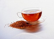 Cup of rooibos tea and fresh rooibos beside it