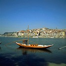 'Rabelos' boats. Port wine transportation boat on Douro river and town skyline. Porto. Portugal