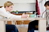 Side profile of a mother and her son sitting at the dining table smiling