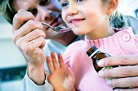 Close-up of a father giving syrup in a spoon to her daughter