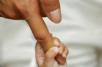 Close-up of a baby boy holding the finger of a person