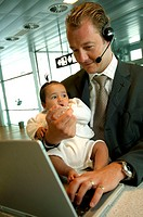 Close-up of a businessman carrying his baby girl and using a laptop