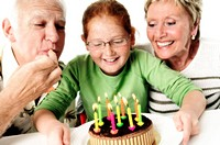 Close-up of a granddaughter celebrating her birthday with her grandparents