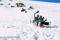 Couple riding on a snow tube
