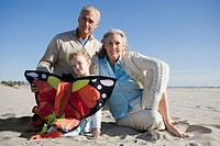 Grandparents and granddaughter holding kite sitting on beach