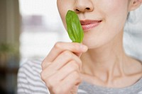 Woman smelling basil leaf