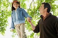Girl walking on wall holding fathers hand