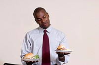 Businessman holding two different plates of food
