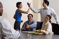 Business colleagues congratulating each other in conference room