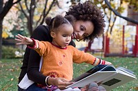 Mother reading to daughter (2-4) in park