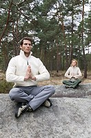 Young man and woman meditating on separate rocks (focus on man)