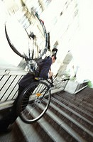 Young man carrying bicycle up steps, side view (focus on man)