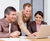 Three business colleagues looking at laptop, smiling