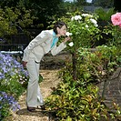 Businesswoman smelling flowers in garden, side view