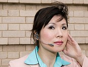 Young woman wearing mobile phone headset, close-up